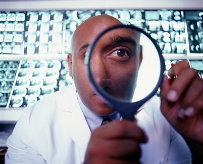 Doctor looking through magnifying glass
