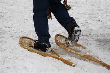Woman wearing old fashioned snowshoes_100391027
